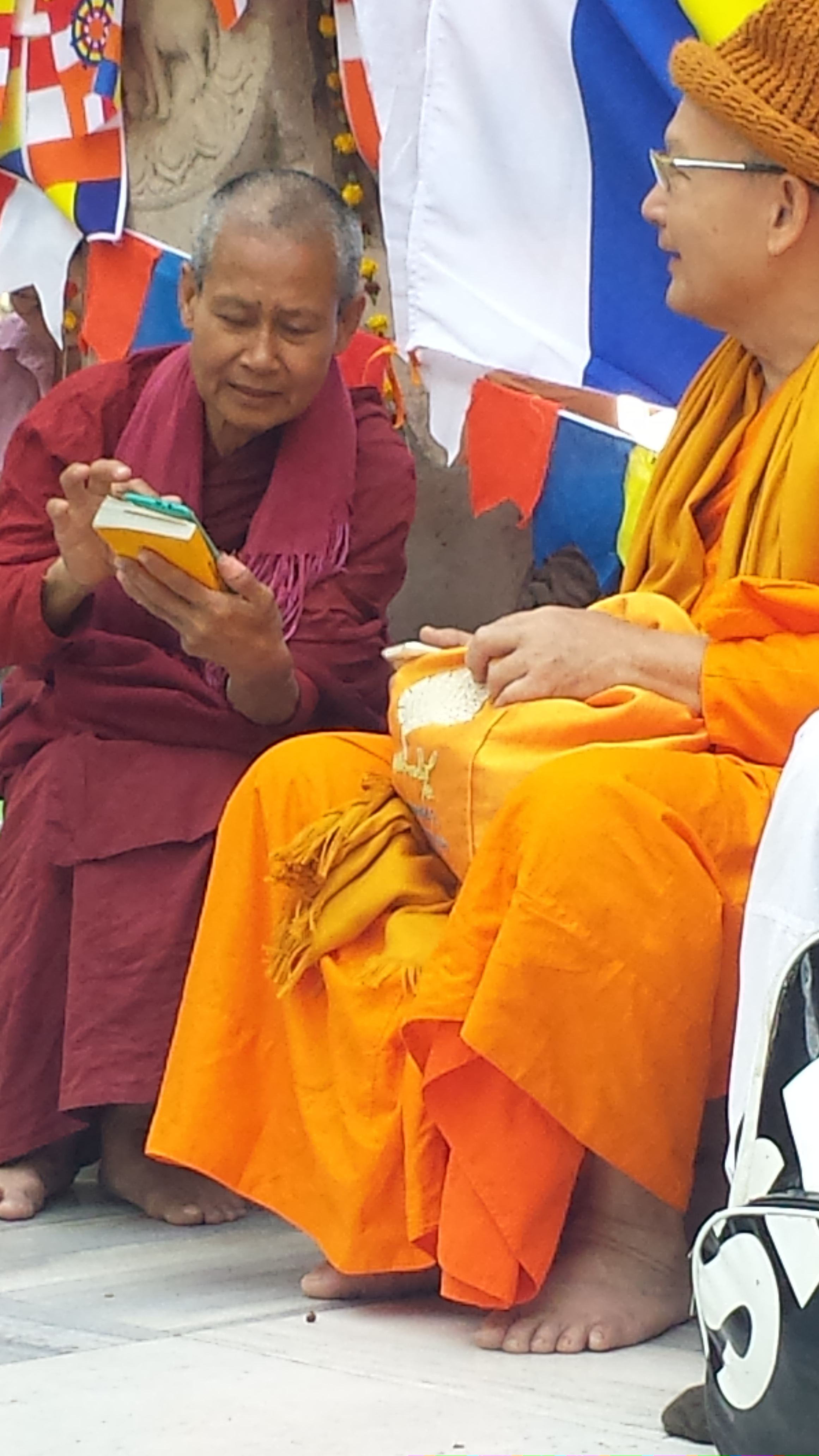 Even the monks and nuns don't take a break from their cell phones at the Maha Bodhi Temple.  FYI:  no cell phones are allowed in the Temple complex, these people are breaking rules!