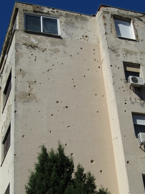 This apartment building is still occupied by tenants, there is no funds to repair the war damage and large bullet holes.