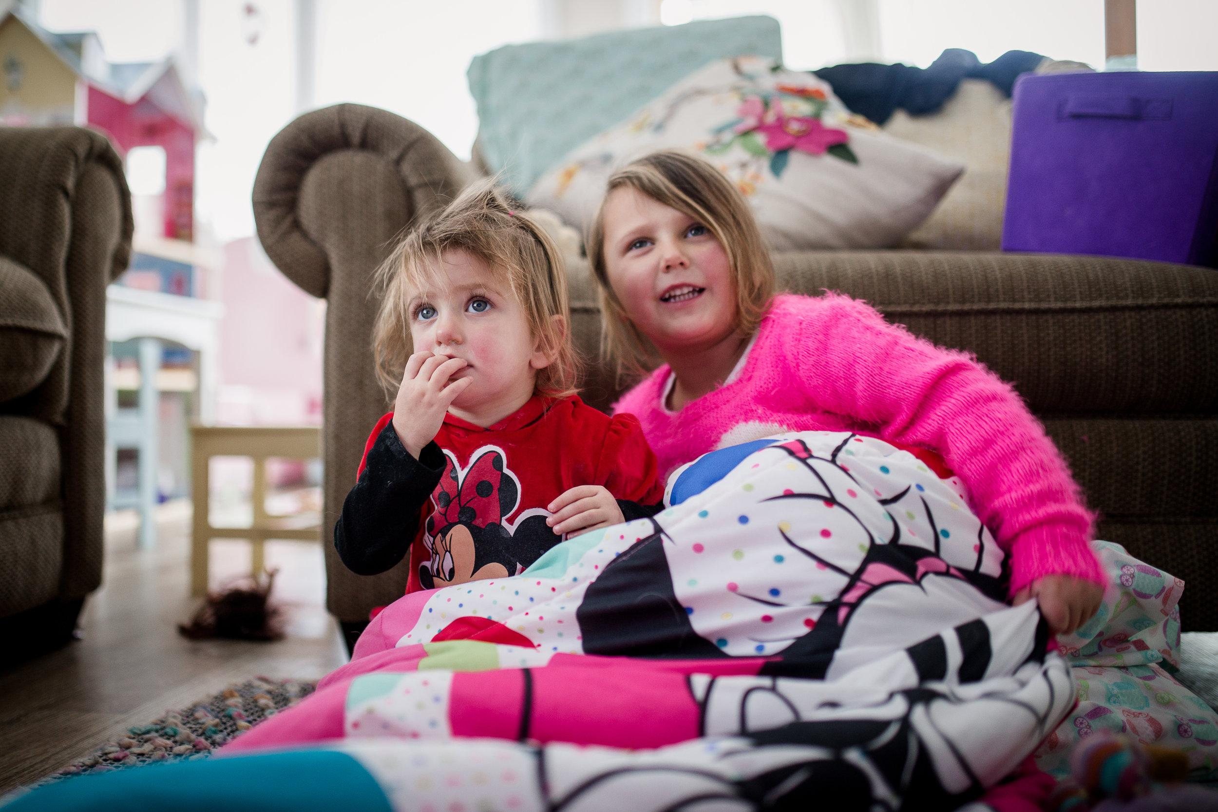 sisters in sleeping bag watching TV