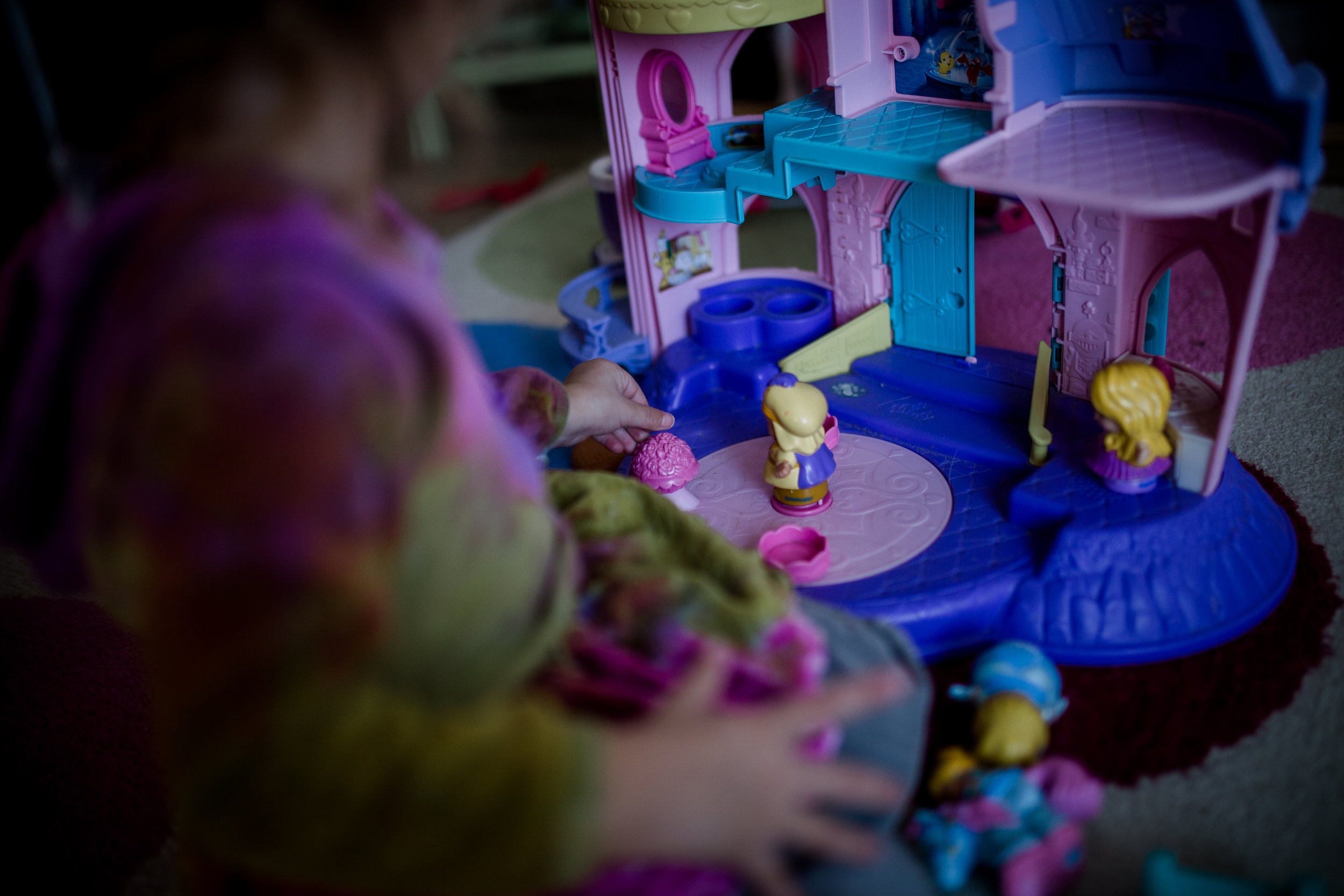 toddler playing with princess dolls