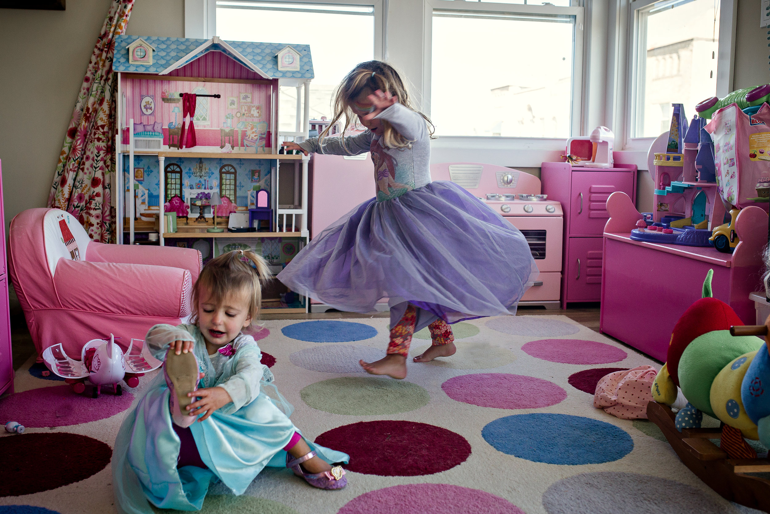 girls playing dress up in pink playroom