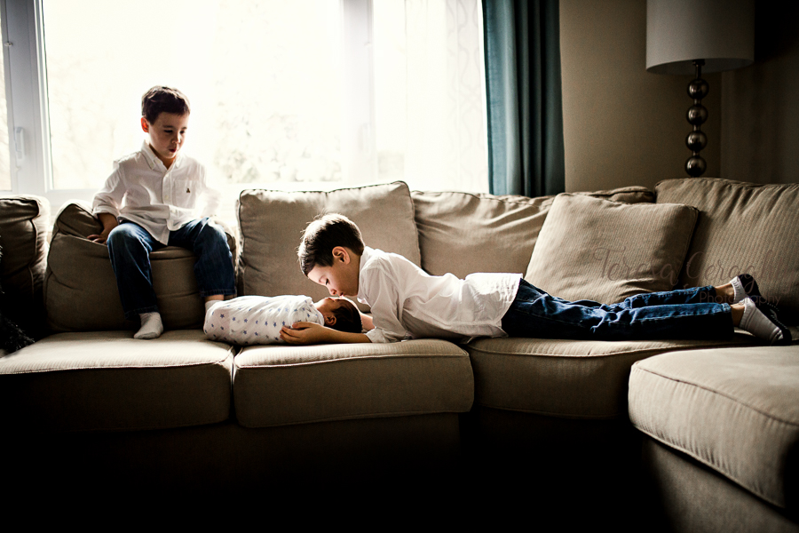 Two boys with newborn baby on a couch