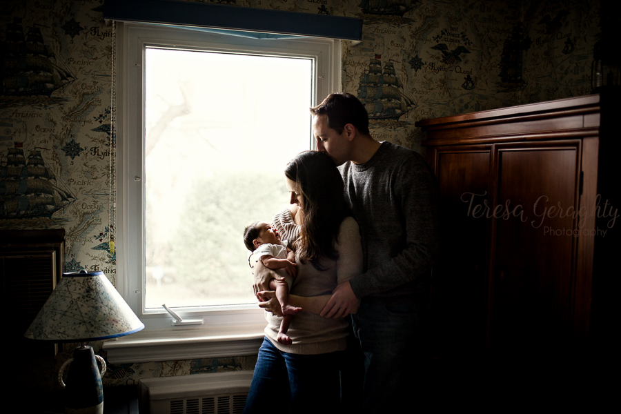 mom and dad by window in a nursery