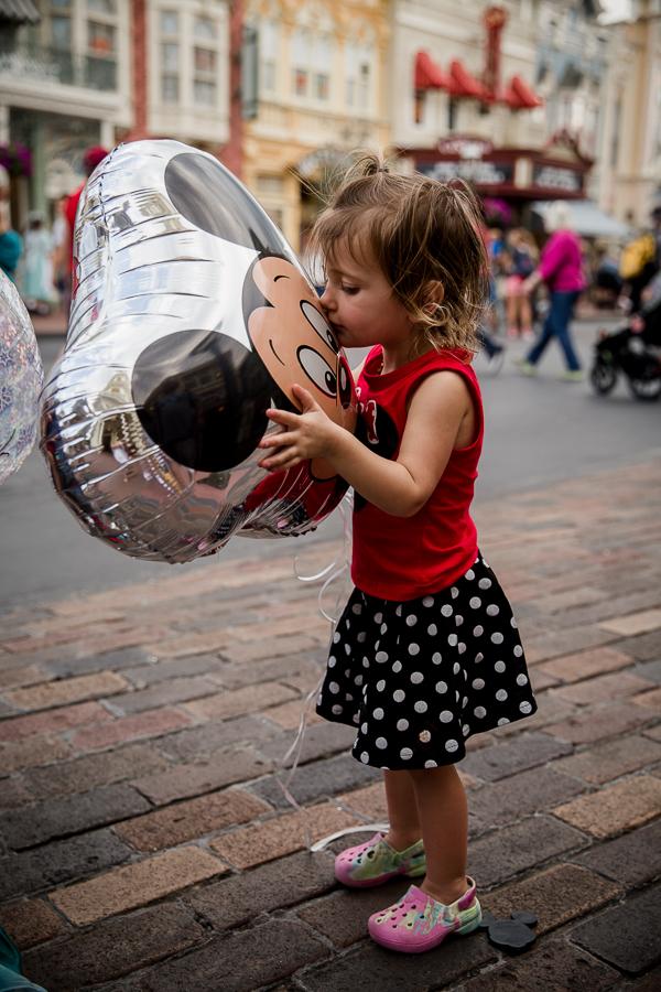 girl kissing mickey balloon