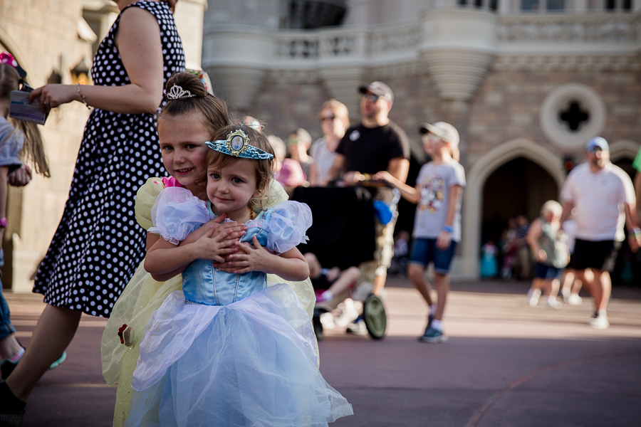 sisters in princess dresses in front of castle in disney