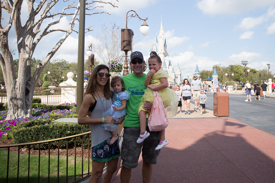 family photo in front of castle at magic kingdom
