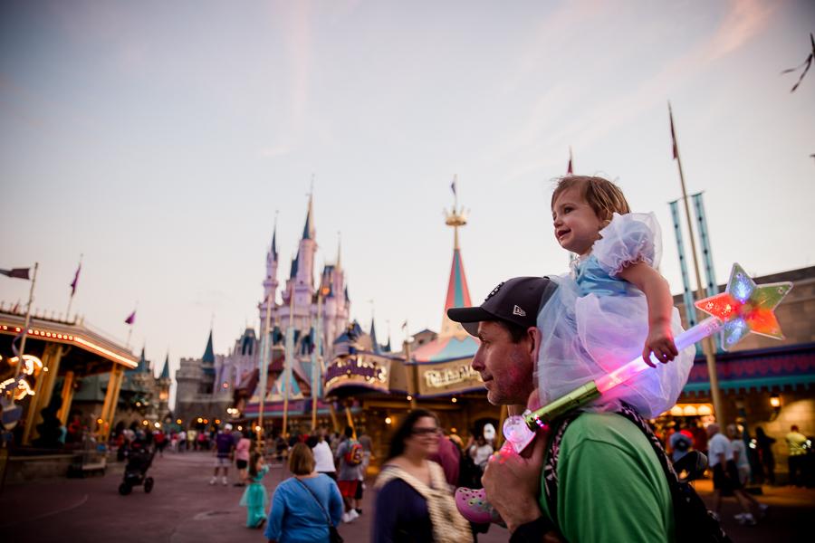 girl on dad's shoulders at magic kingdom