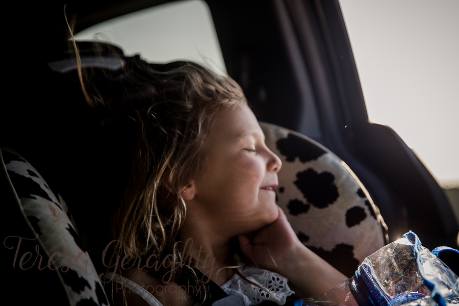 girl in car seat smiling at wind in hair
