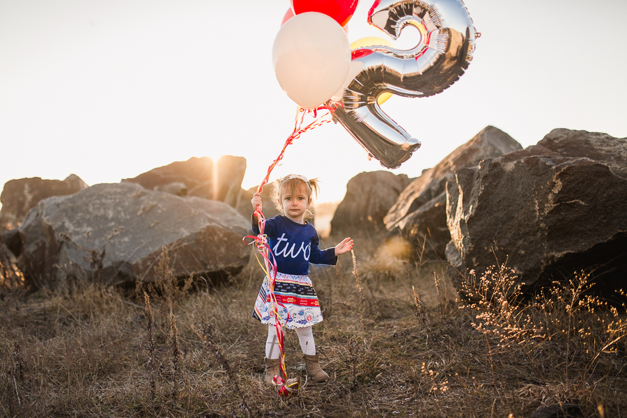 Two year old birthday portraits in sunset with baloons