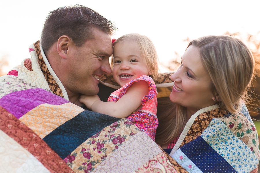 family wrapped in quilt hugging