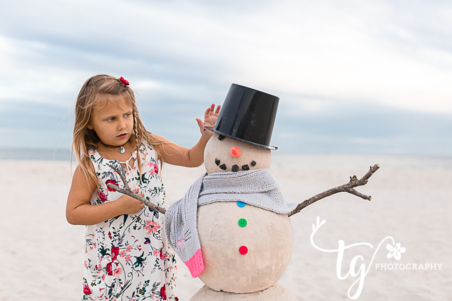 girl putting hat on snowman