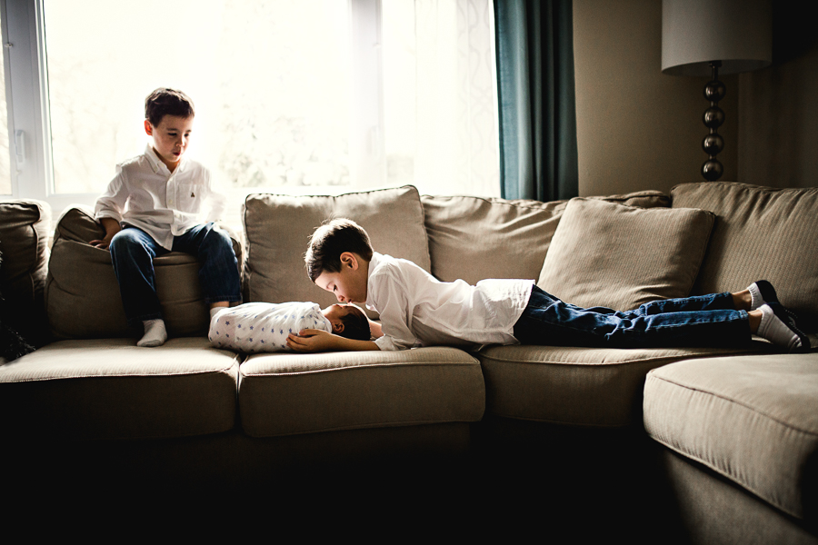 brothers looking at baby on couch