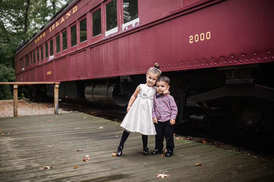brother and sister in holiday clothes next to red long island rail road classic train