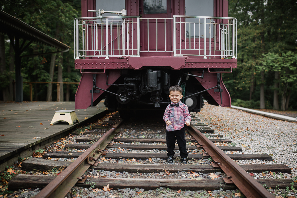 toddler on train tracks with vintage red train behind him