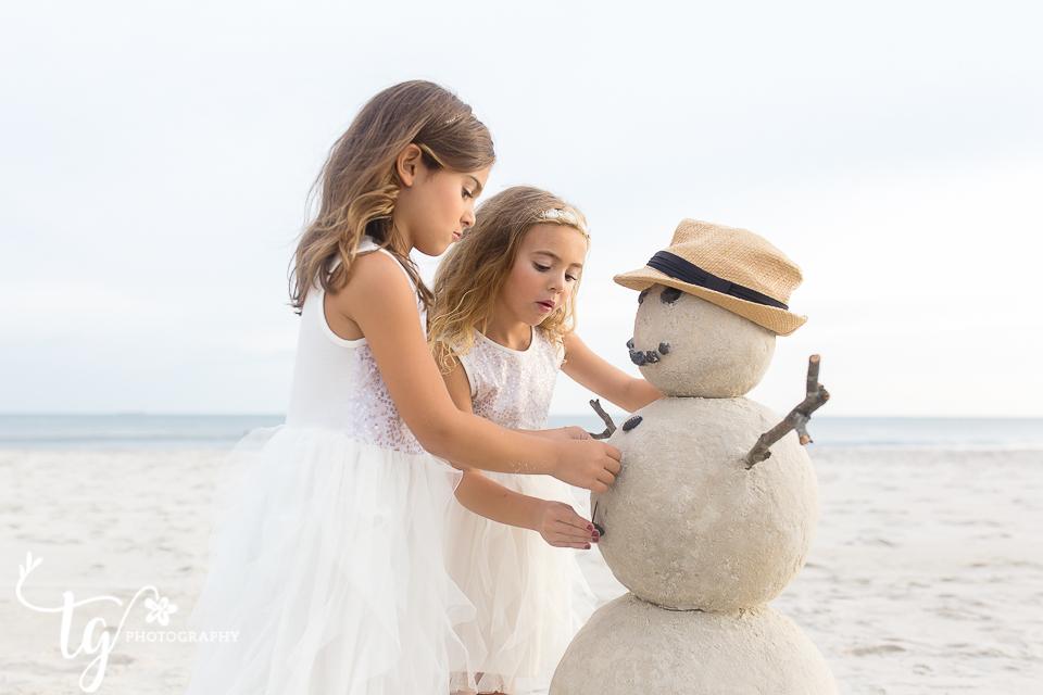 girls decorating sand snowman in white dresses
