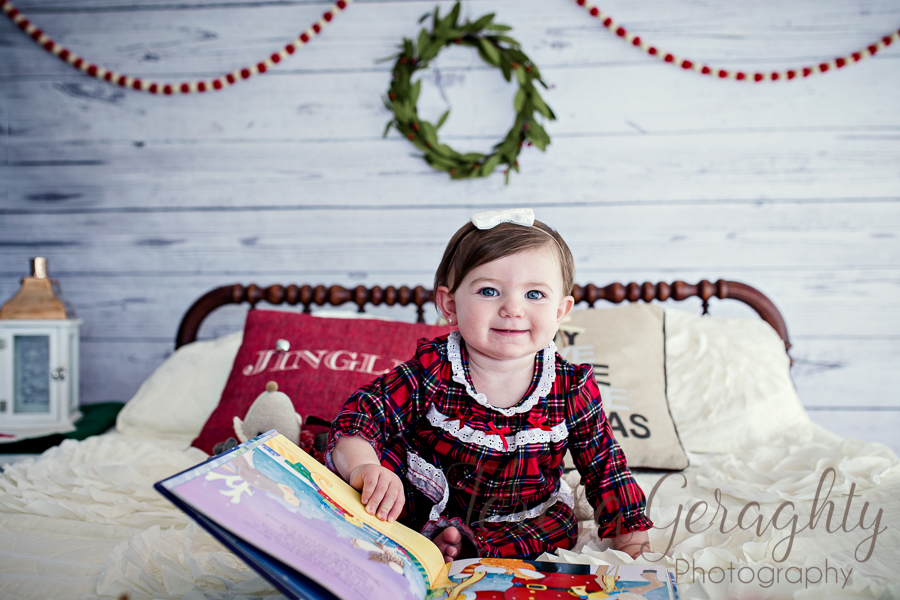 toddler on white rustic bed with plaid pajamas on for christmas photos