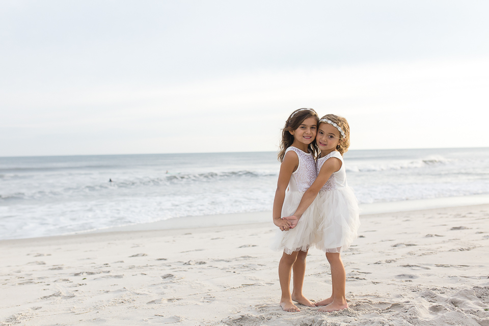 sisters in white dresses on the beach holding hands