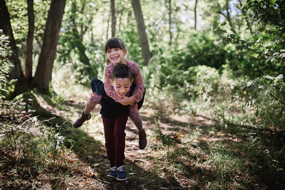 siblings piggy back in park