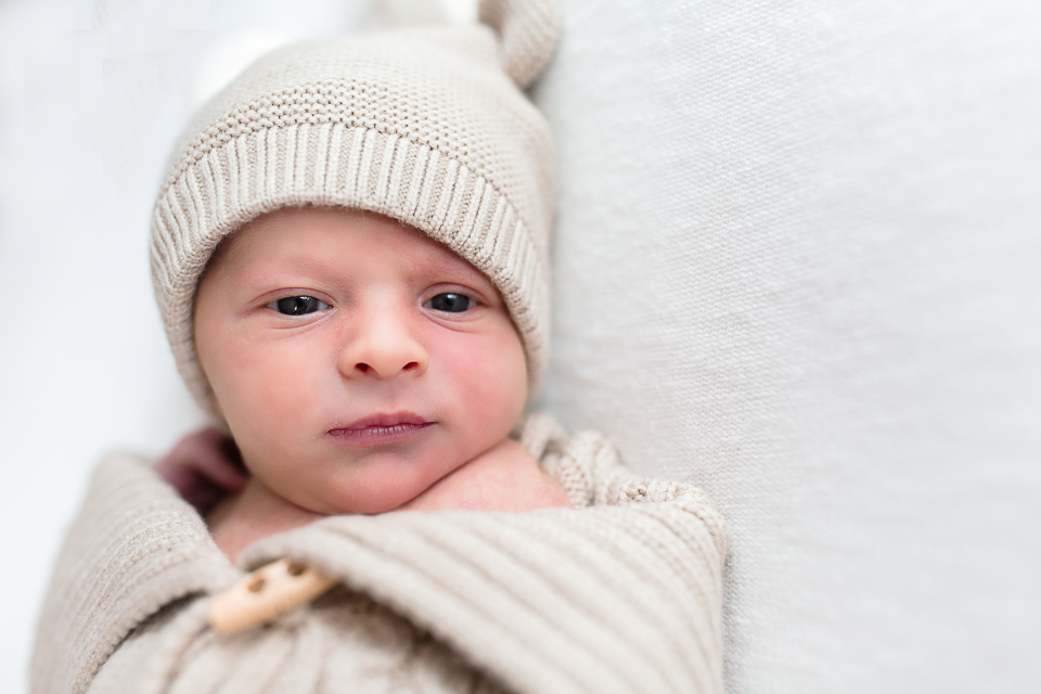 baby in tan cable knit deer outfit on white background