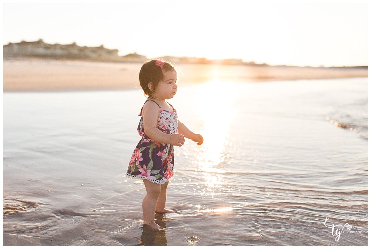 Little girl in blue romper in the ocean with sunrise behind her