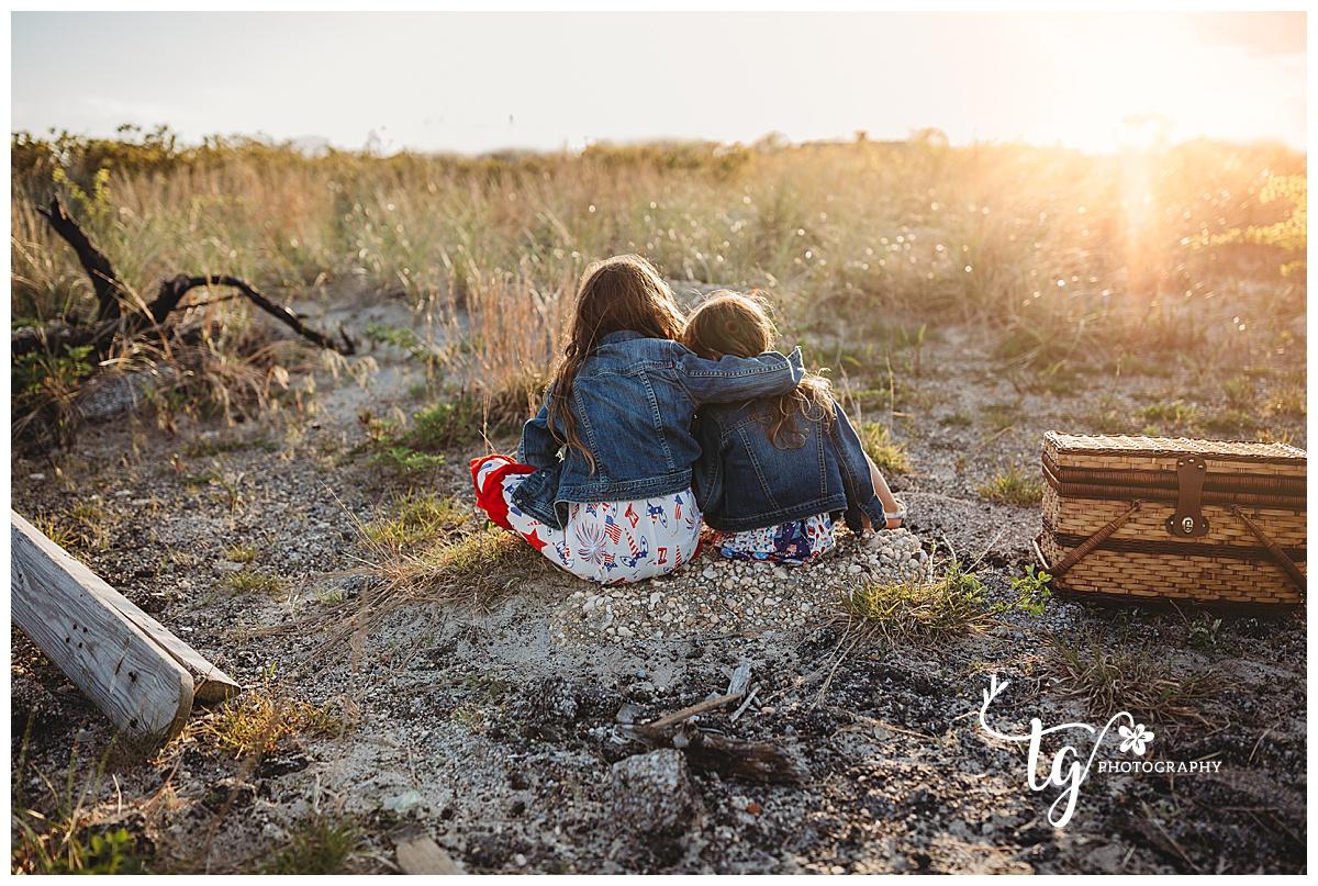 toddlers facing sunset hugging while sun sets