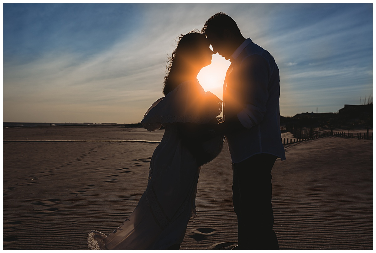 silhouette of pregnant woman and husband at sunset