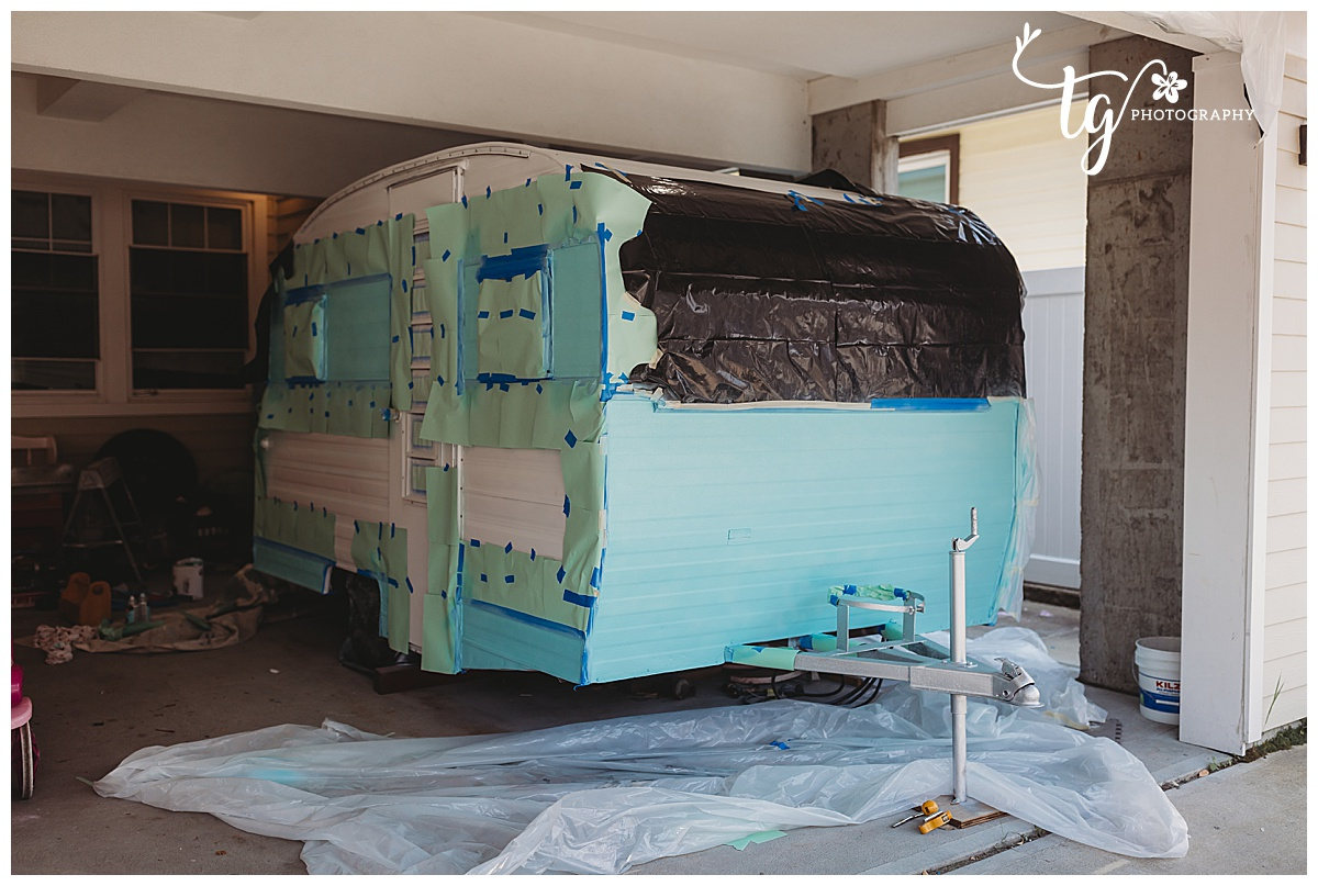man painting the stripe of a 1969 Playmor camper