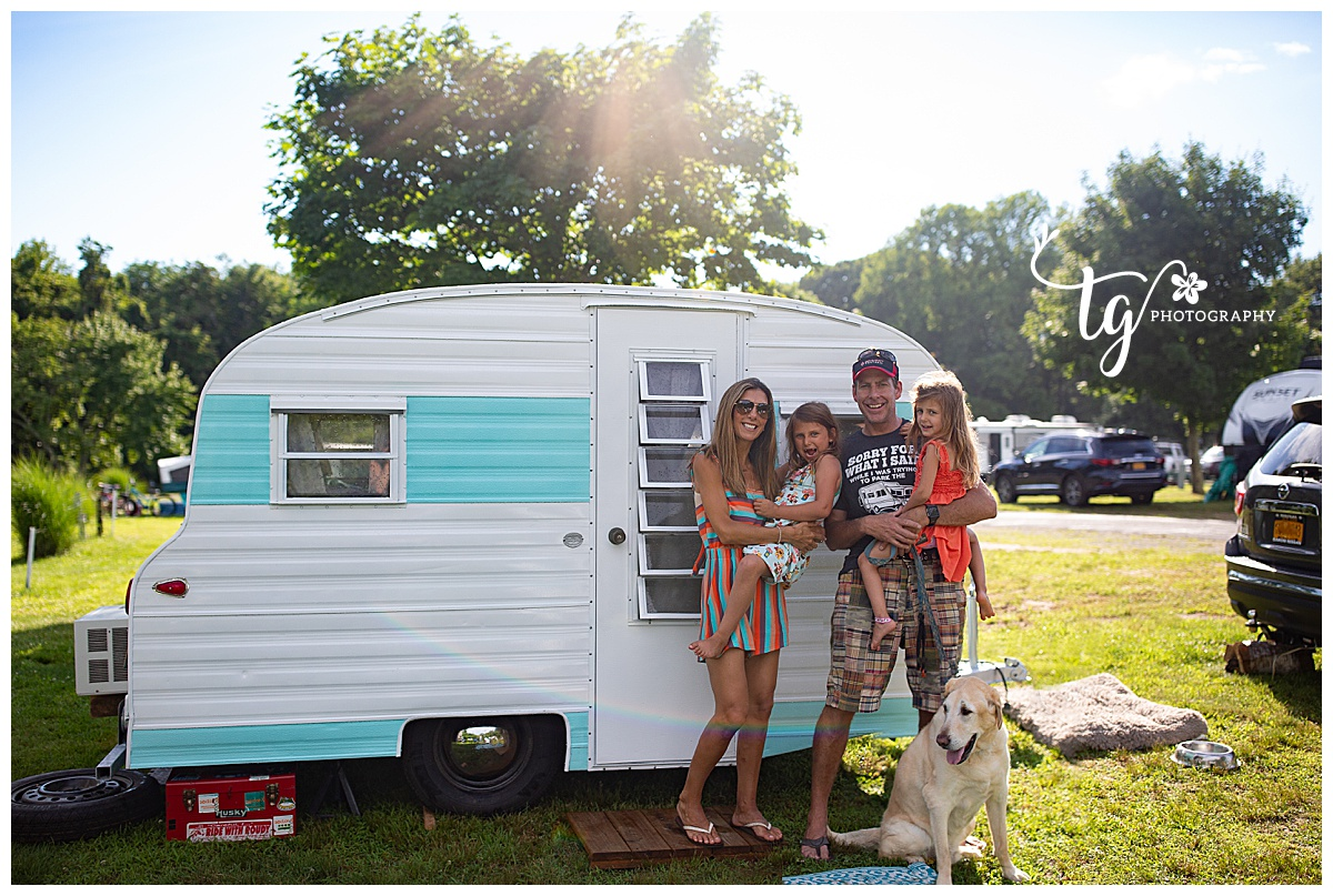 family in front of a 1969 playmor camper on a campground