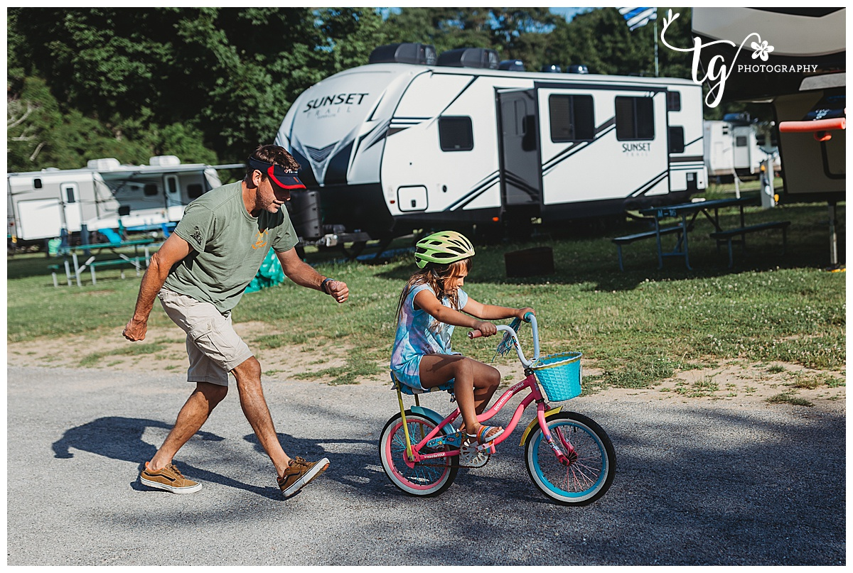 little girl learning to ride a bike at a campground d