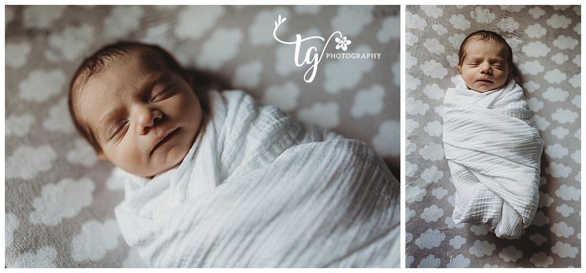 baby swaddled in whit receiving blanket on grey cloud fabric