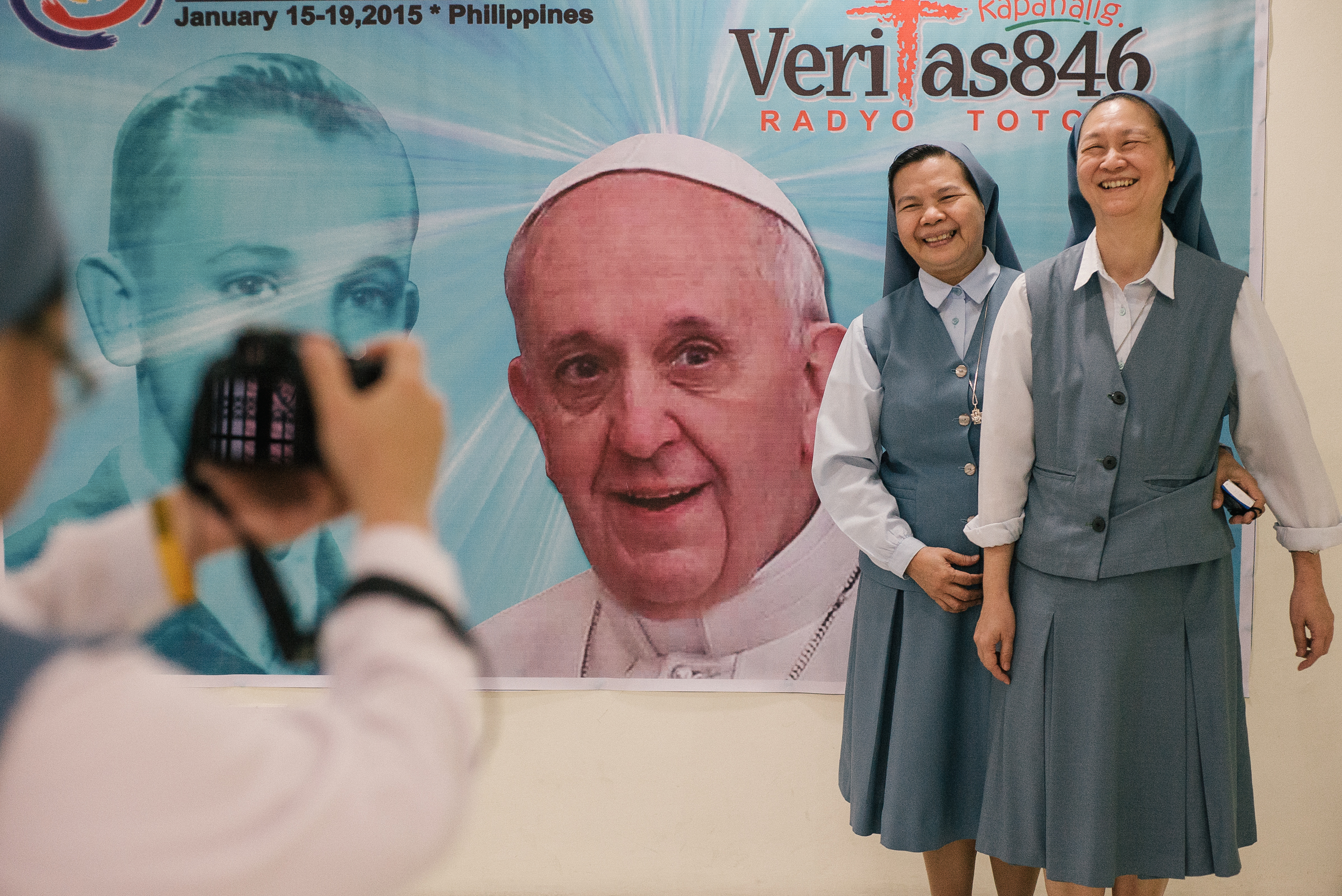 Nuns have their picture taken beside the face of Pope Francis printed on a tarpaulin.