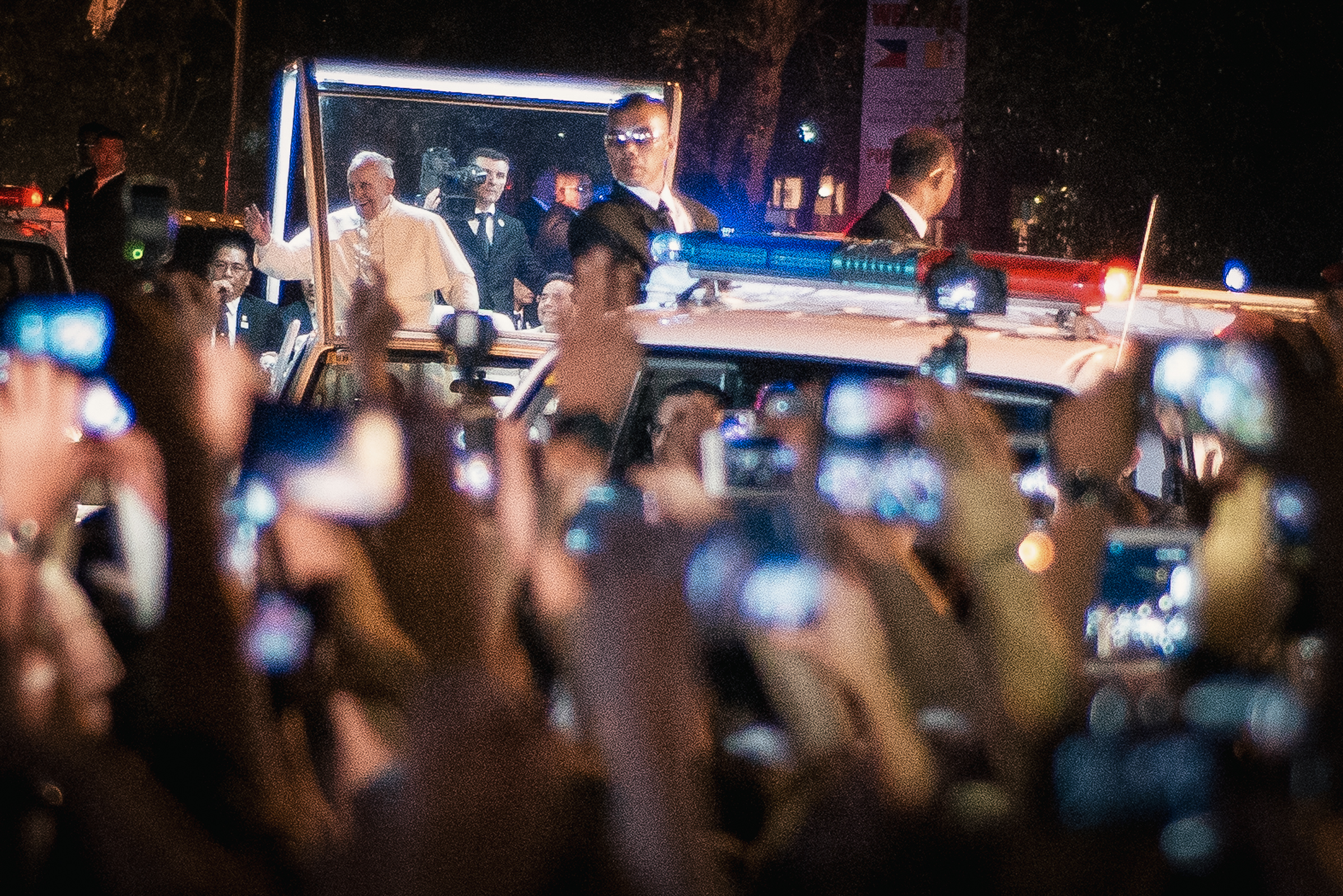 Filipino faithfultakepictures of Pope Francis on board hismobilealongRoxas Boulevard on the night of his arrival on January 15, 2015.  Filipino faithfultakepictures of Pope Francis on board hismobilealongRoxas Boulevard on the night of his arrival on January 15, 2015.