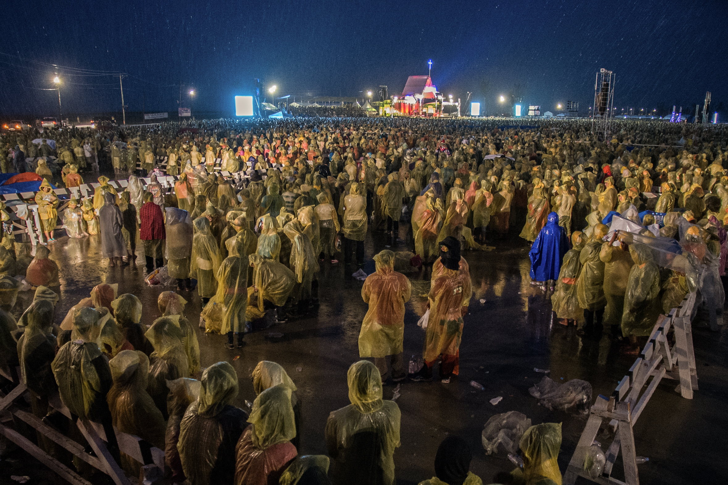 Amid strong winds and rain brought bytyphoon Amang,  pilgrims gathernear the Tacloban airport the night before Pope Francis' Holy Mass for the victims of Typhoon Yolanda.