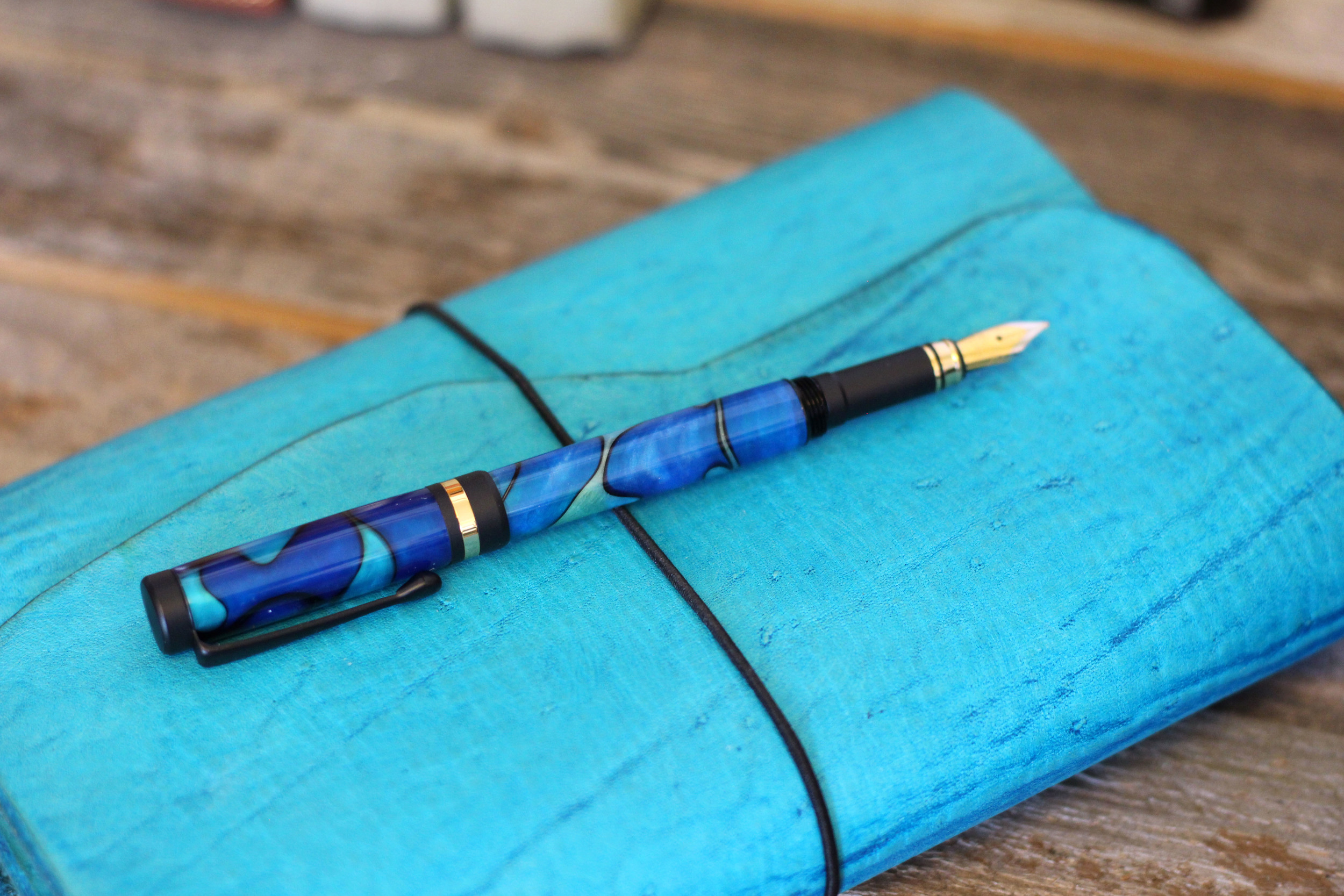 Wrap Leather Quill with a Natural Edge in the Color Turquoise Trail.  Fountain Pen is Caribbean Cool.