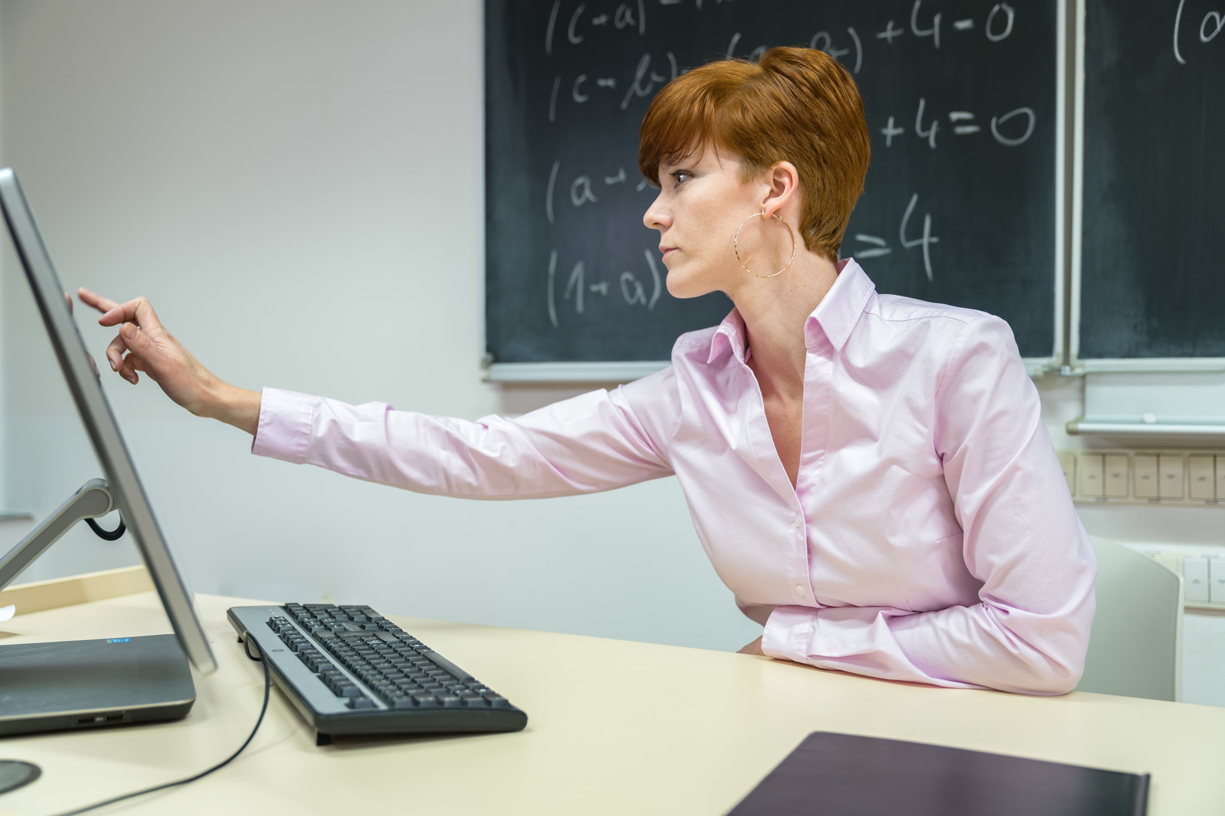 young woman prepares a teaching lesson in class on her computer