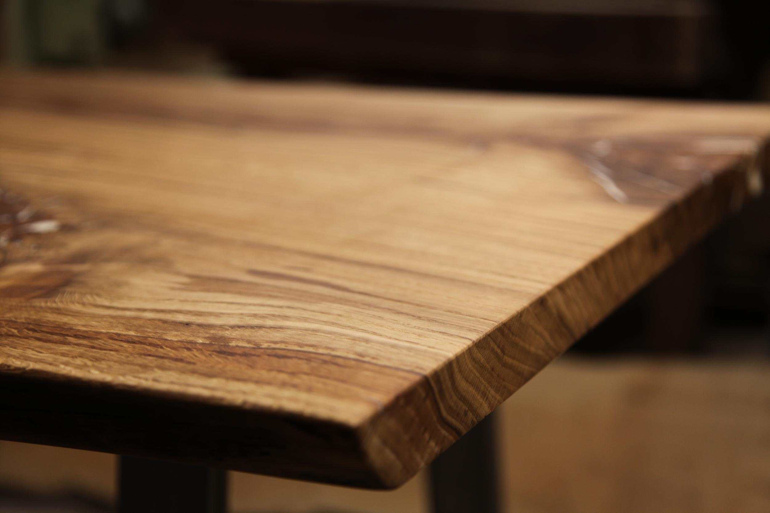 Schreibtisch aus einer durchgehenden Eichenplatte mit Baumkante;die Astlöcher sind mit fluoreszierendem Material gefüllt.