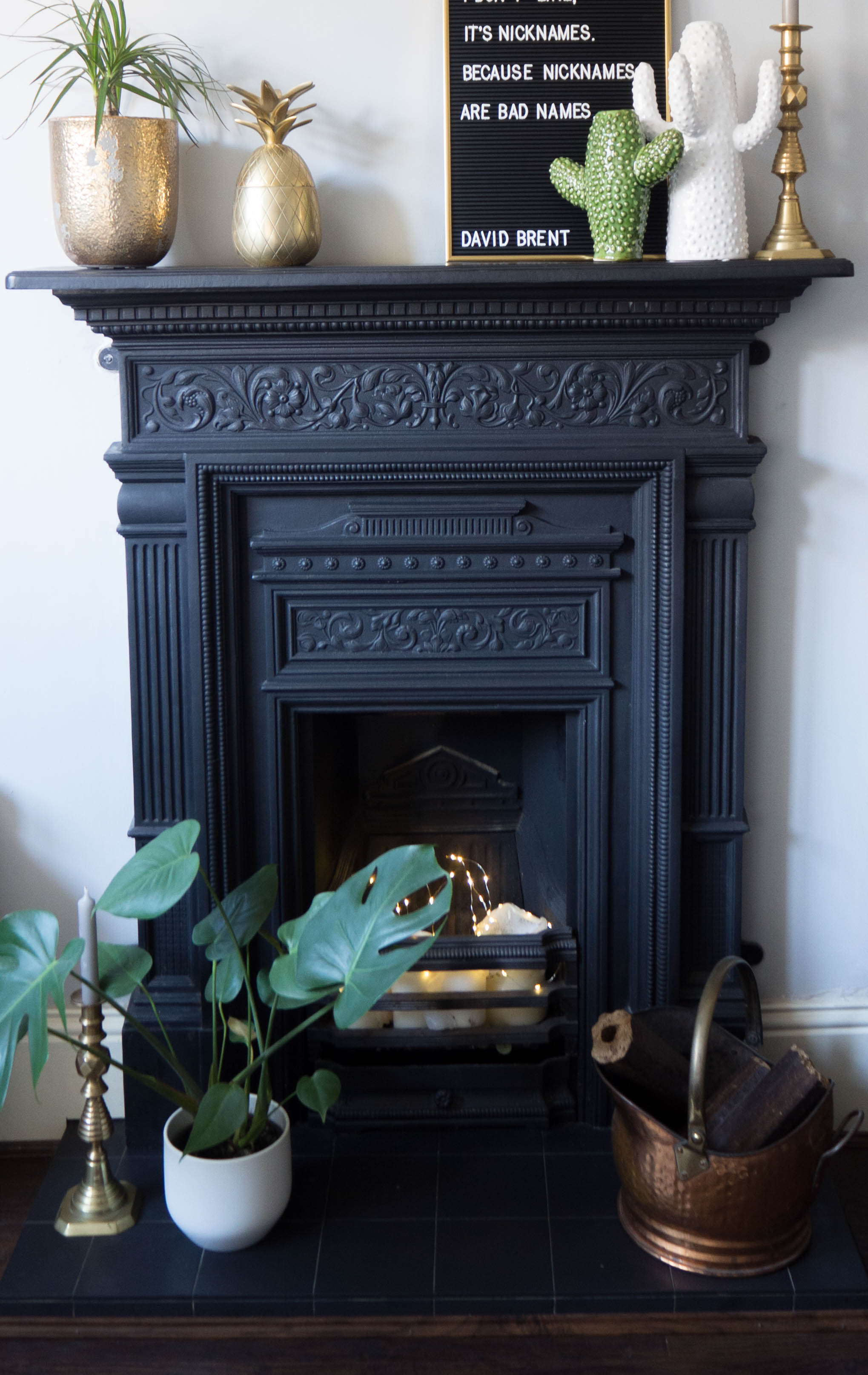 My cast iron fireplace surround with ceramic cactus vases, brass pineapple and a letter board.