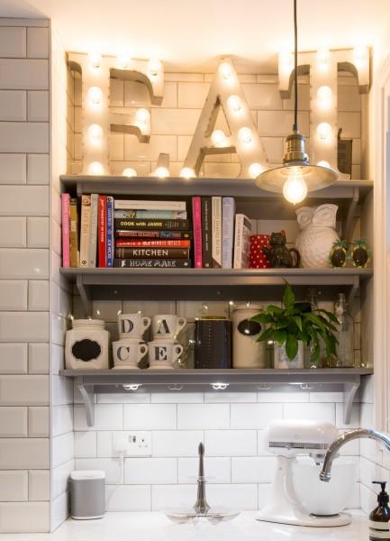 Kitchen shelves and light bulb EAT sign.