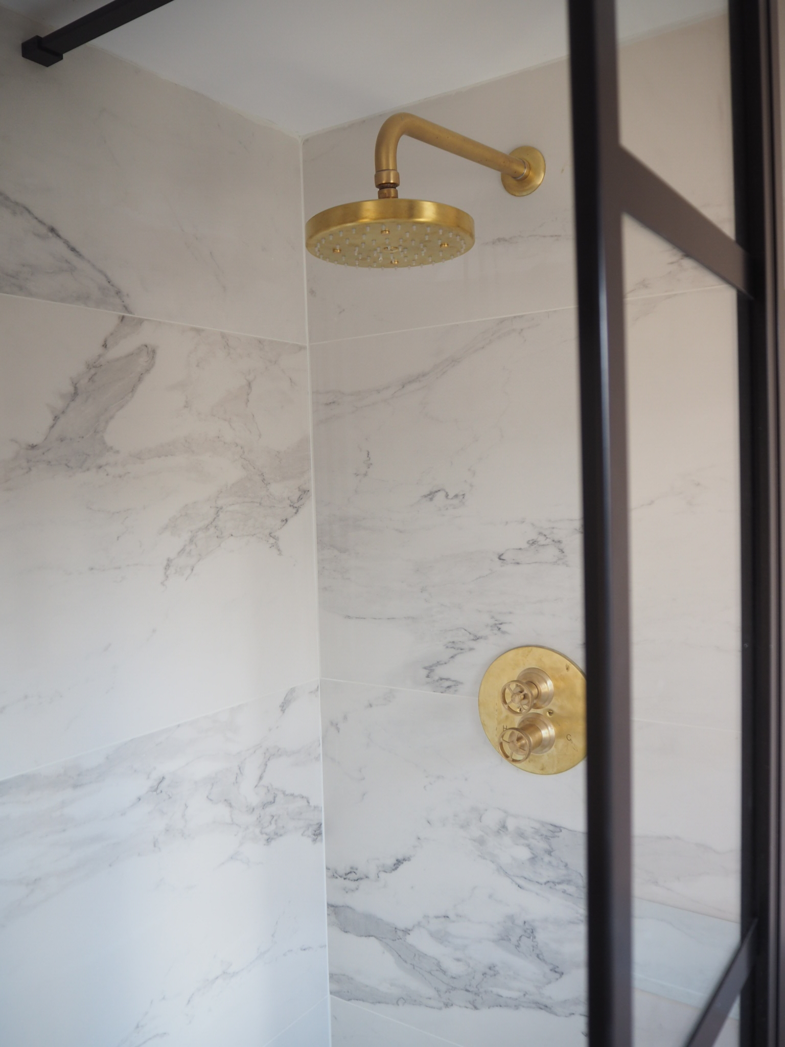 Carrera marble tileS,  Acme shower from Aston Matthews and Black metal shower frame from Drench