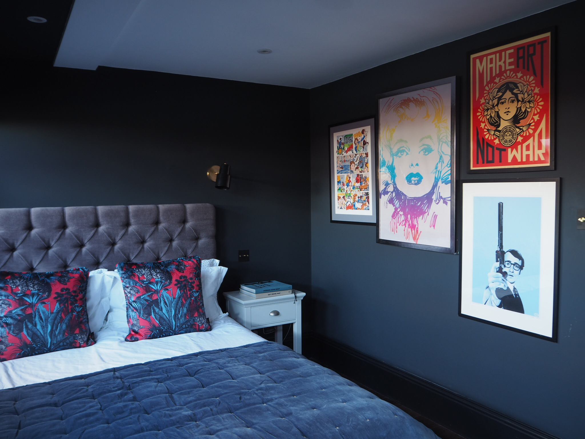 Gallery wall in bedroom and Farrow and Ball Railings bedroom, with Divine Savages cushions