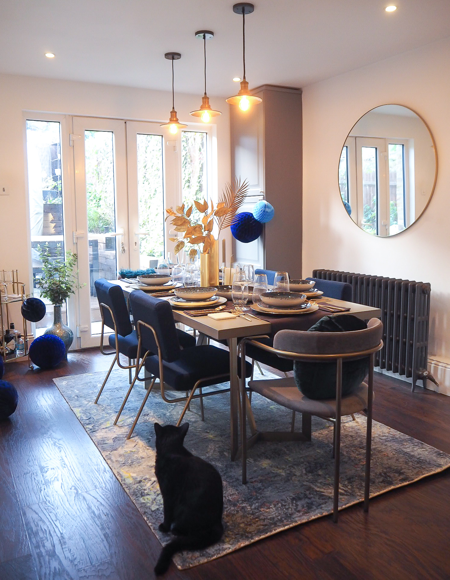 Tower concrete top dining table    £899 , West Elm;   Orion Blue rug   £499, West Elm.   Blue frame wire dining chair   £199, West Elm.   Round velvet cushion     £39 on the chair from West Elm.