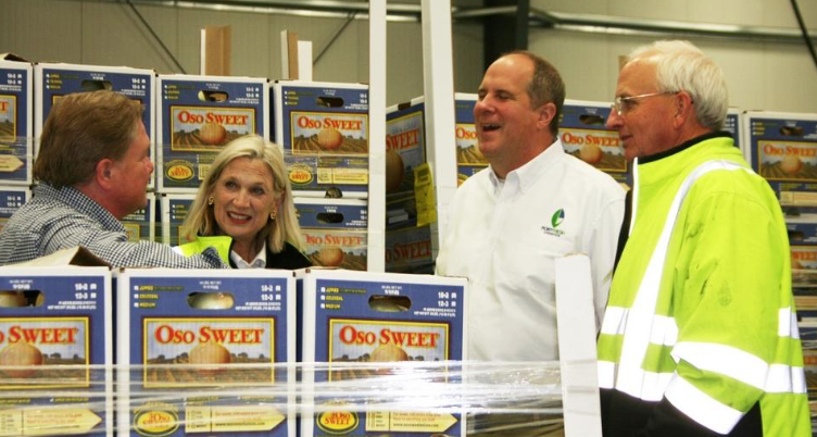 From left, Ken Burke, PortFresh vice president of client relations; Rebecca George Ogden, president; Brian Kastick, CEO and state Agriculture Commisssioner Gary Black are surrounded by boxes of onions during a plant tour. (G.G. Rigsby/Effingham Now)