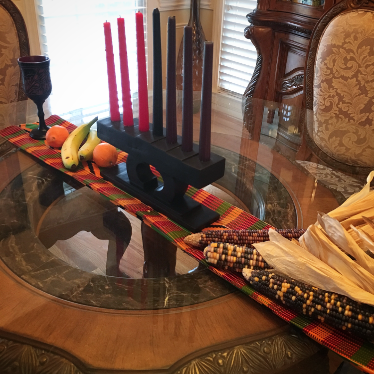 Traditional symbols of Kwanzaa include: A mat/cloth representing the foundation of African traditions, crops to represent the harvest and toil of our ancestors, the kinara to hold the candles, seven candles (one for each Kwanzaa principle) in the colors of the Pan-African flag, a unity cup to be filled with a drink shared by those celebrating, and corn symbolizing the children (without the house) and their futures.