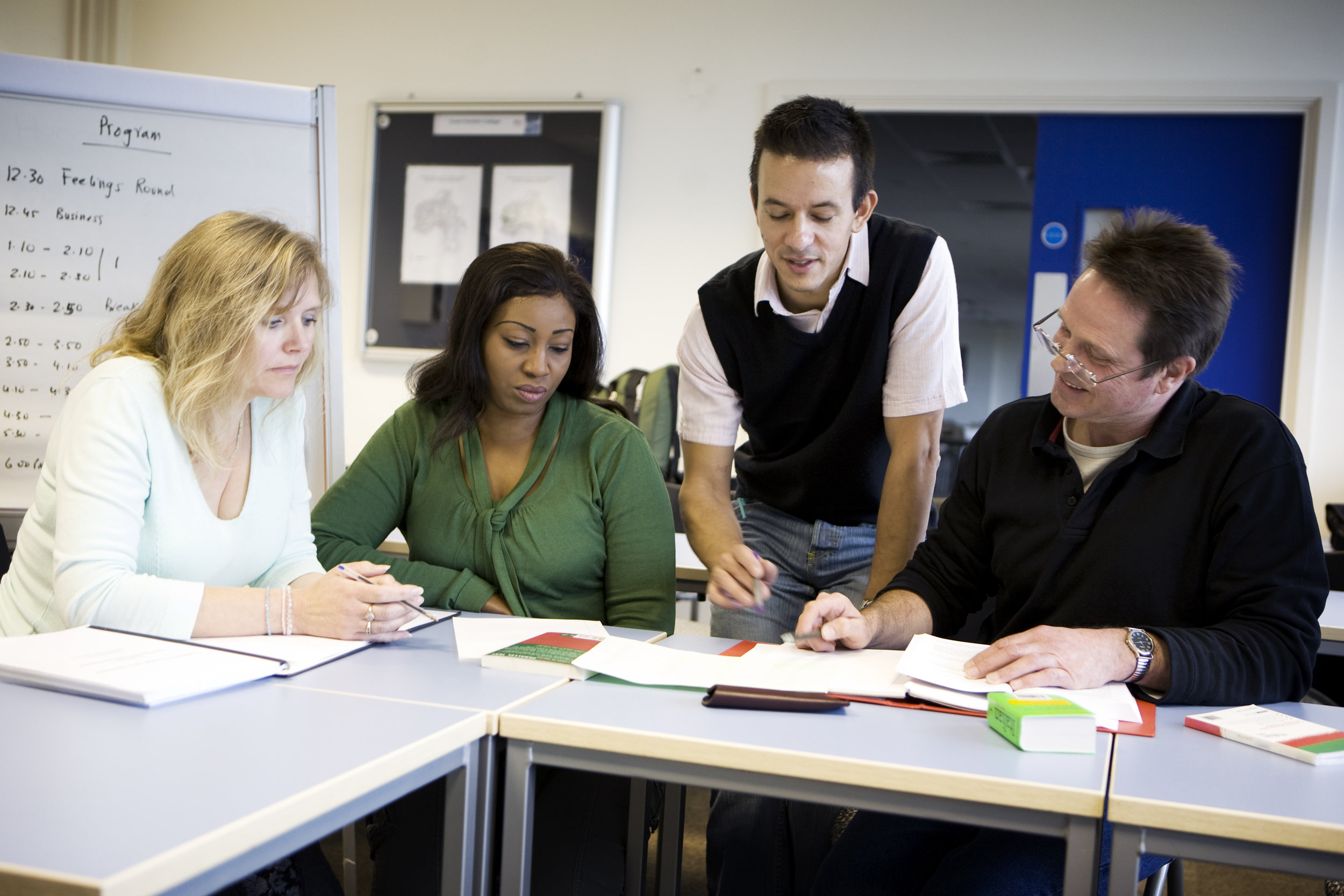 adult-education-a-teacher-helping-a-group-of-mature-students-157395895_4278x2852.jpeg