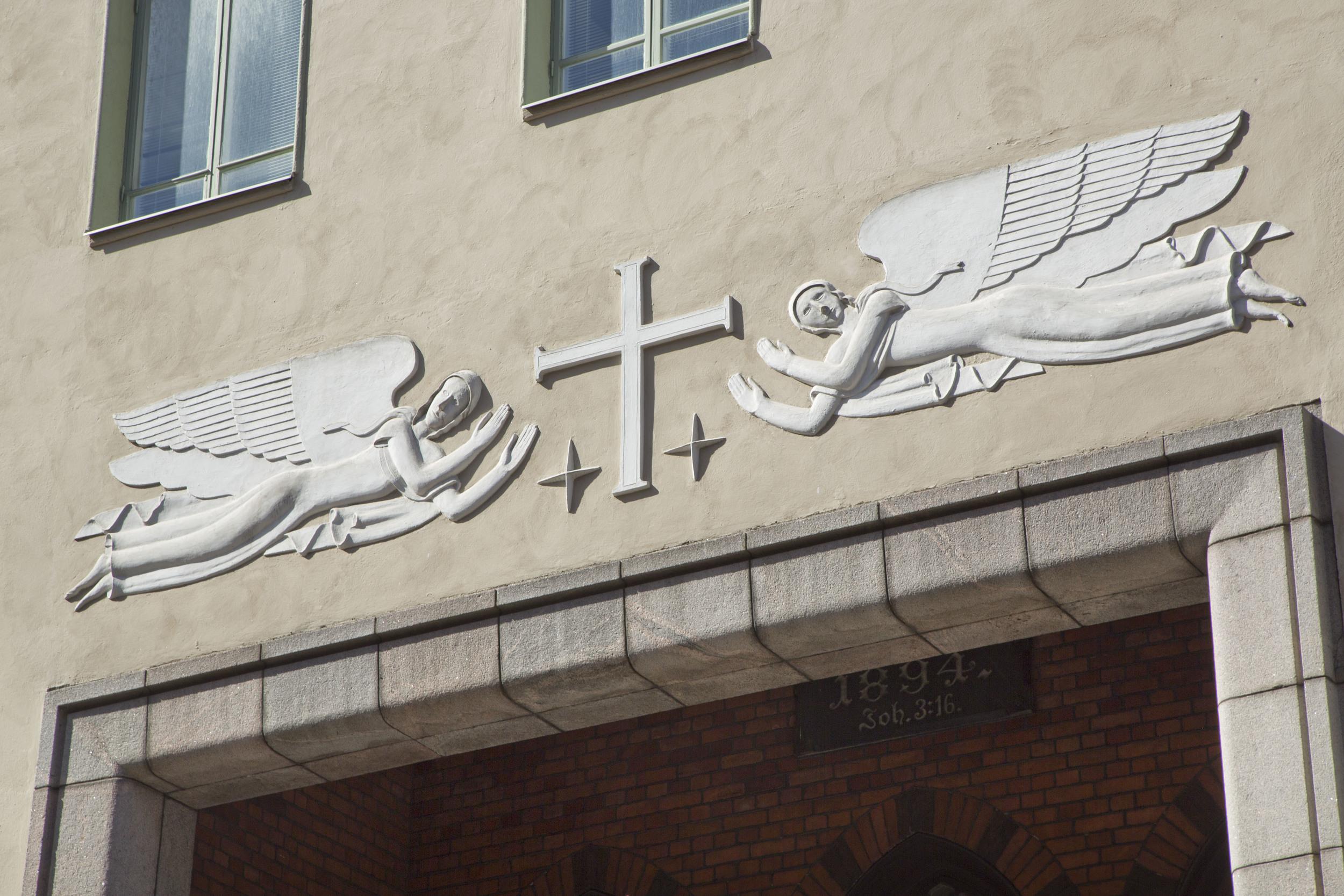 Kuvassa Gunnar Finnen taiteilemat enkelireliefit Luther-kirkon sisäänkäynnin yläpuolella. Kuva: Olli Häkämies.