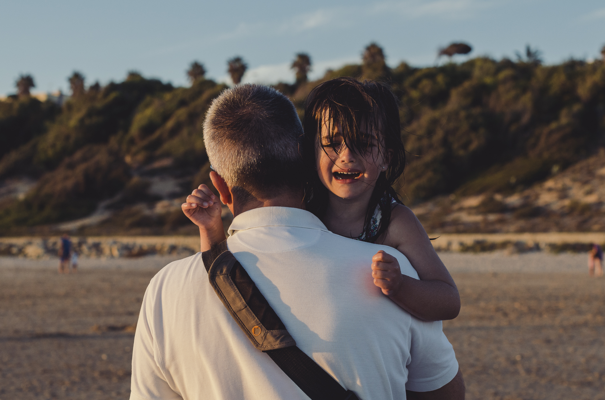 Crying girl with dad at the beach