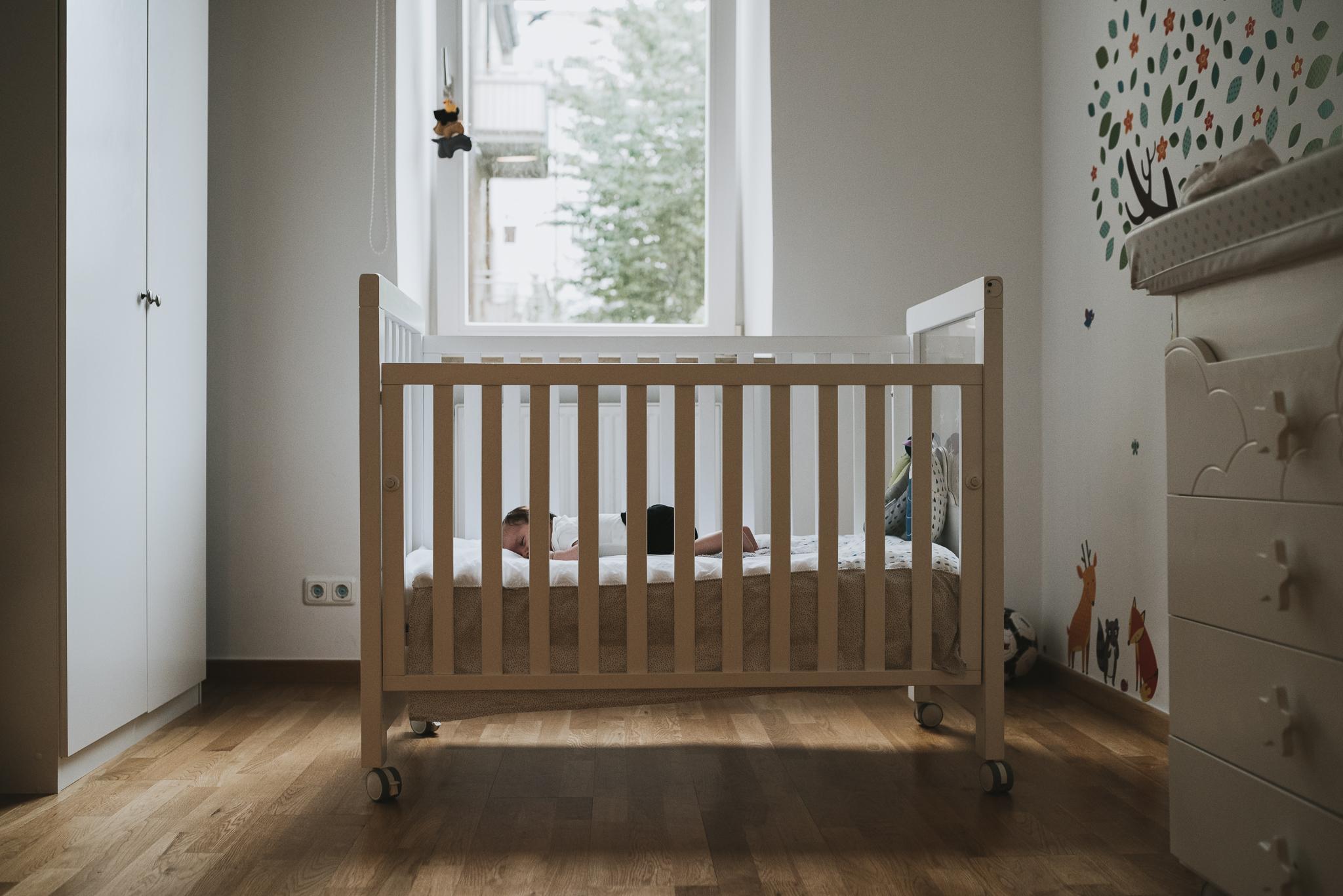 Newborn baby in crib in bedroom.jpg