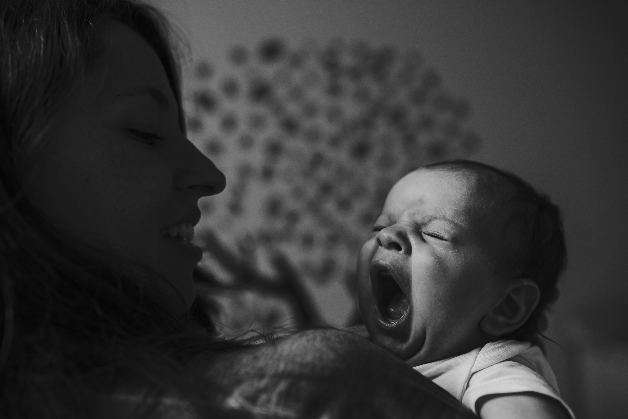 Newborn baby yawing in mom's arms.jpg