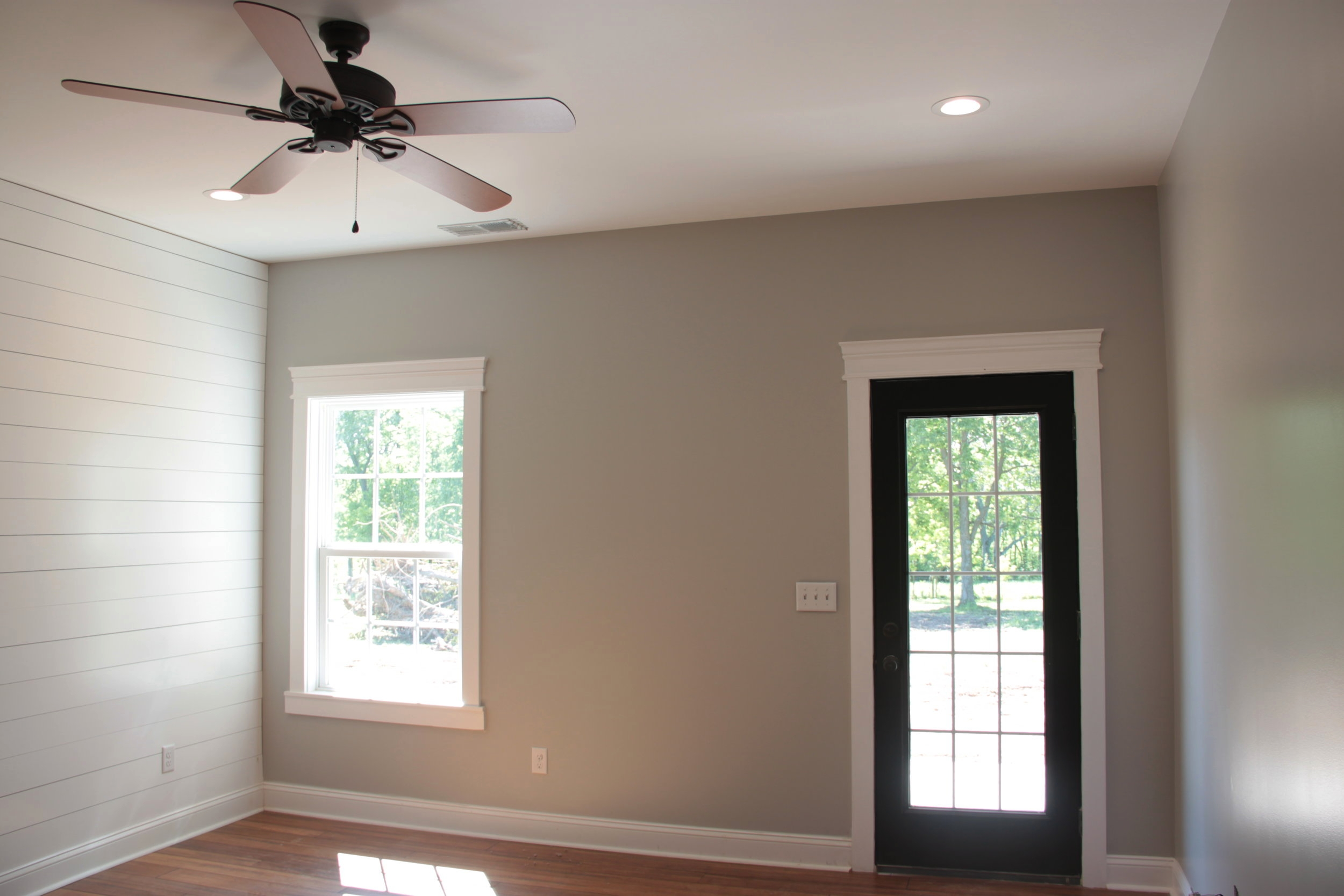 The master bedroom also features shiplap along with beautiful trim, and a bold color choice for the exterior patio door.