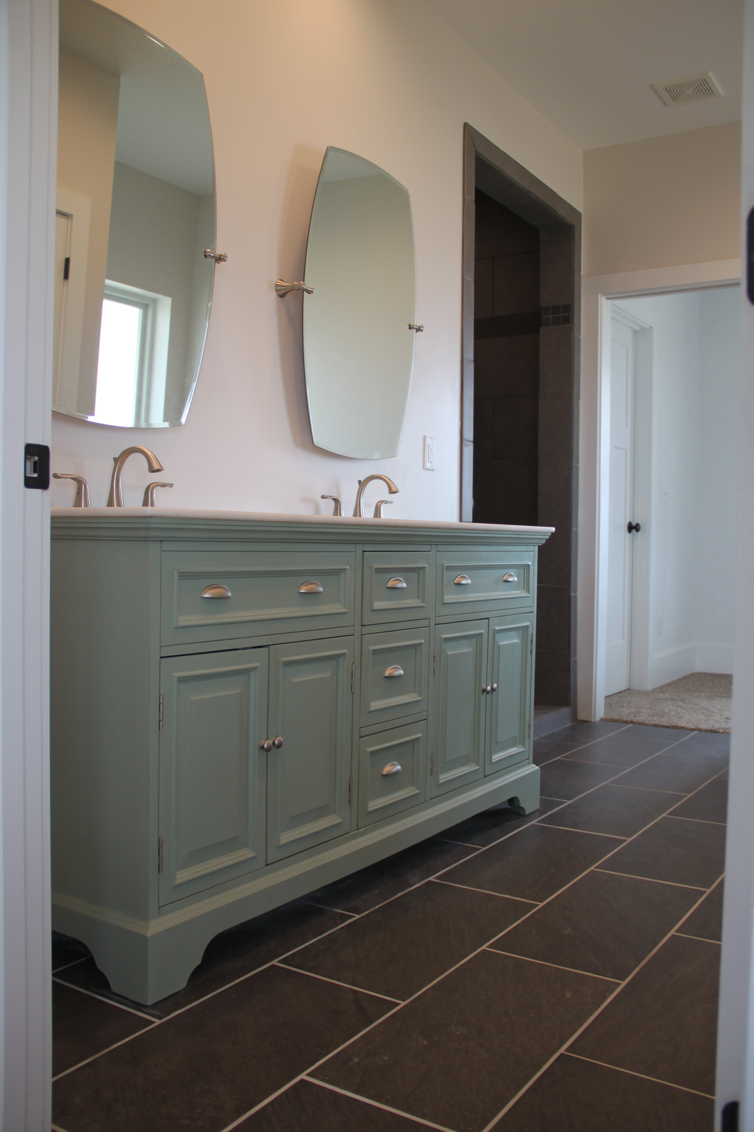 The Master Bath has a soaker tub and a shower with multiple shower heads. The beautiful charcoal tile is accented with the mint green double vanity.
